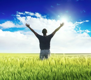 man standing on the green field under blue sky